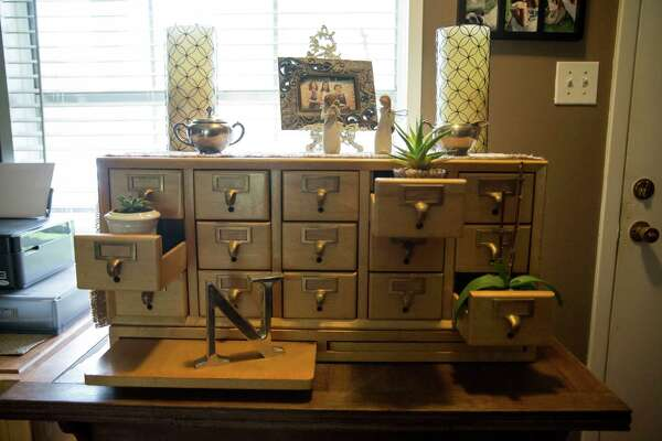 The an old wooden library card catalog case in Janie and Jason Norris' home, which is primarily furnished with items found in thrift stores.