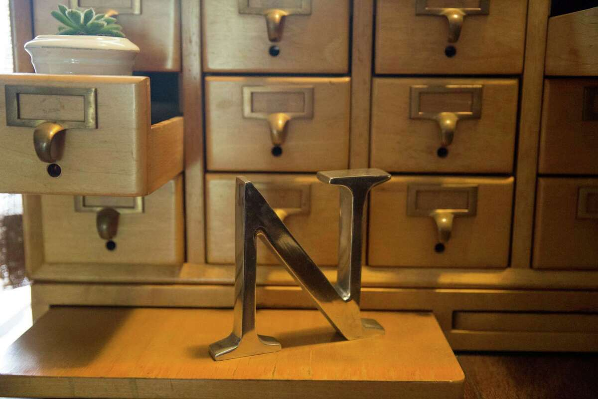 A repurposed large chrome letter N originally used to display stockings decorates an old wooden library card catalog case.