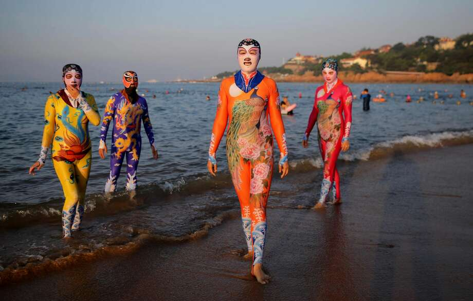 Women and men wearing siamesed facekinis pose on beach on August 29, 2016 in Qingdao, Shandong Province of China. Facekini has been China\'s popular beach trend and the latest siamesed facekini designed with various patterns like dragon, phoenix and peacock and many others catered to women and men\'s pleasure. Different from the old facekini protecting head only, the siamesed facekini kept your head and upper body away from sunshine. Photo: VCG/VCG Via Getty Images