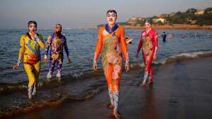 Women and men wearing siamesed facekinis pose on beach on August 29, 2016 in Qingdao, Shandong Province of China. Facekini has been China\'s popular beach trend and the latest siamesed facekini designed with various patterns like dragon, phoenix and peacock and many others catered to women and men\'s pleasure. Different from the old facekini protecting head only, the siamesed facekini kept your head and upper body away from sunshine.