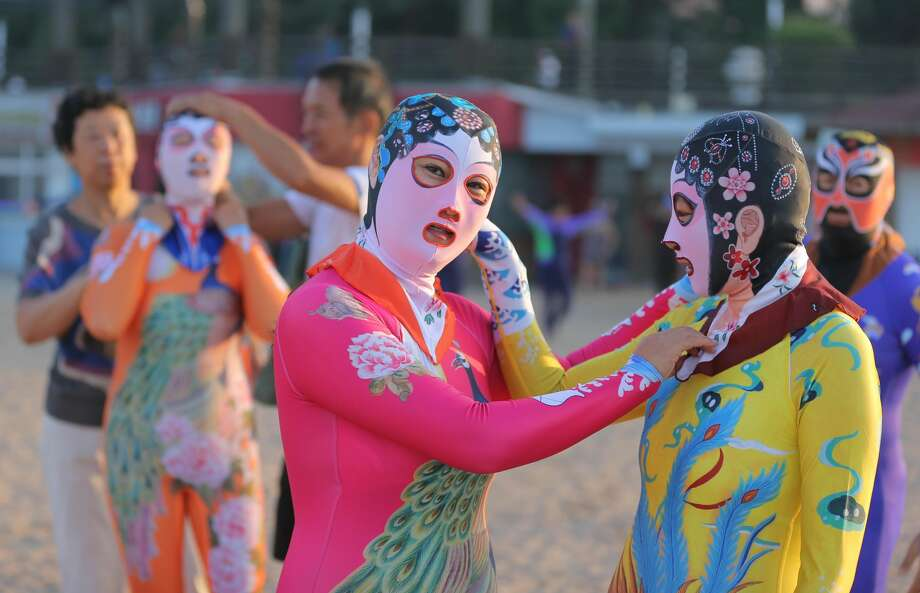 Women wearing siamesed facekinis play on beach on August 29, 2016 in Qingdao, Shandong Province of China. Facekini has been China\'s popular beach trend and the latest siamesed facekini designed with various patterns like dragon, phoenix and peacock and many others catered to women and men\'s pleasure. Different from the old facekini protecting head only, the siamesed facekini kept your head and upper body away from sunshine. Photo: VCG/VCG Via Getty Images