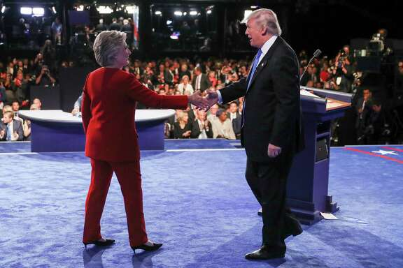 Democratic presidential nominee Hillary Clinton and Republican presidential nominee Donald Trump, who stumbled badly, shake after the presidential debate at Hofstra University.
