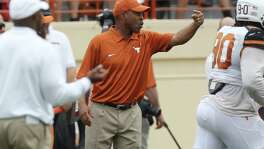 Texas defensive coordinator Vance Bedford (center) gestures to his players at the 2014 Orange-White spring game in Austin on April 19, 2014.