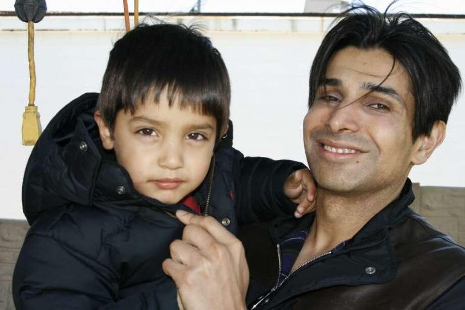 Taseer Badar, right, with his son, Daaniyal, at the grand opening celebration of Swash Car Wash in Atascocita.