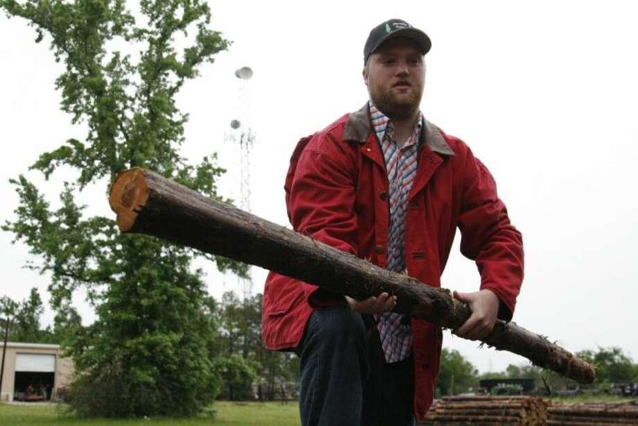 Zach French lifts a cedar post at his Discount Cedar Log yard in Humble.