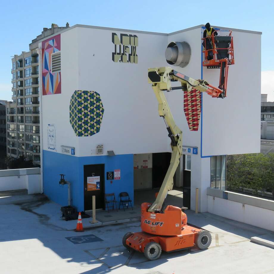 """Ezra Eismont works on the """"Upper Wall,"""" high above Third Street. Books, Mike """"Bam"""" Tyau and Dead Eye Dave of ICU Art also worked on the section. Photo: Photo By Stash Maleski/ICU Art."""