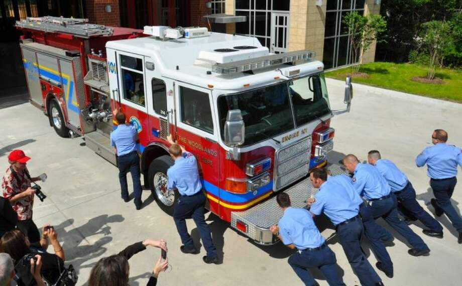 "The Woodlands Fire Department firefighters engage in the tradition of pushing the engine into the newly rebuilt Central Station. The tradition dates back to the 19th century when fire departments had horse-drawn ""engines"" that had to be pushed back into the station after a service call."