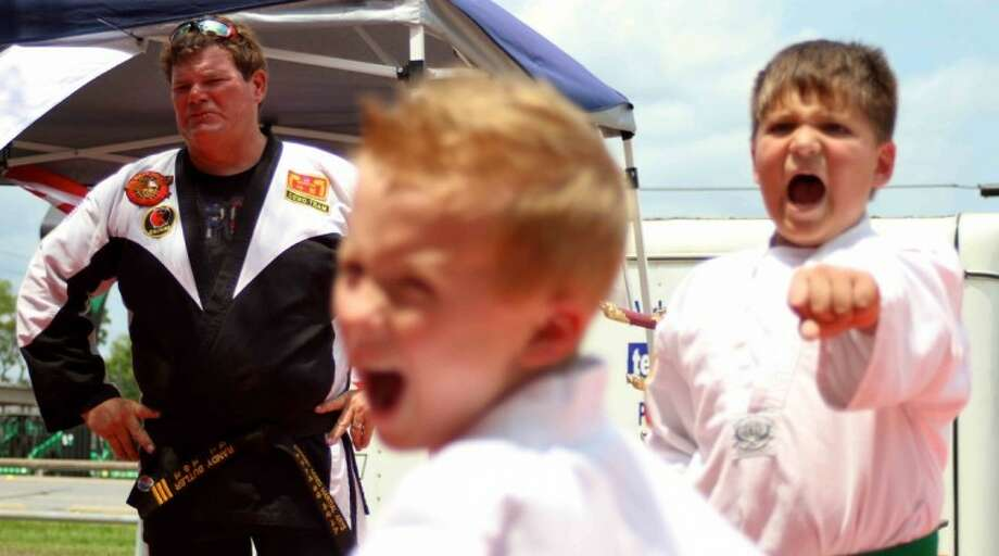 Black belt instructor Randall Butler, left, looks on during a demonstration by Crosby Mixed Martial Arts at Kids Day, sponsored by Balance Chiropractic, in Crosby on Saturday, June 9. Photo: Jason Fochtman