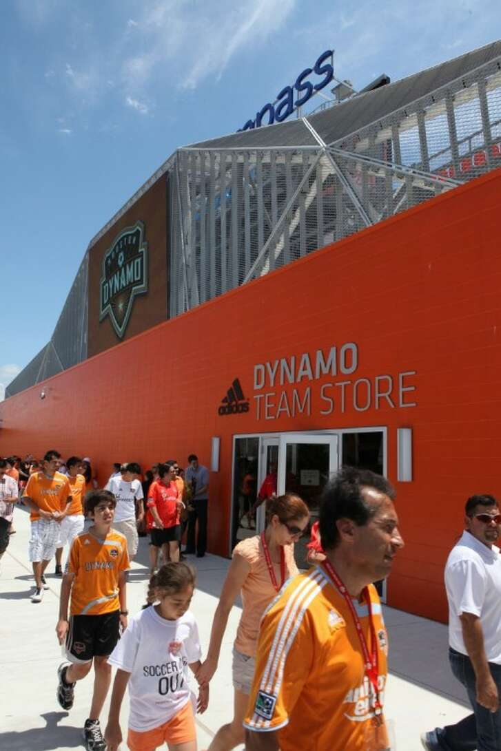 Houston Dynamo fans walk by the Dynamo Team Store at the inaugural match against D. C. United at BBVA Compass Stadium in downtown Houston.