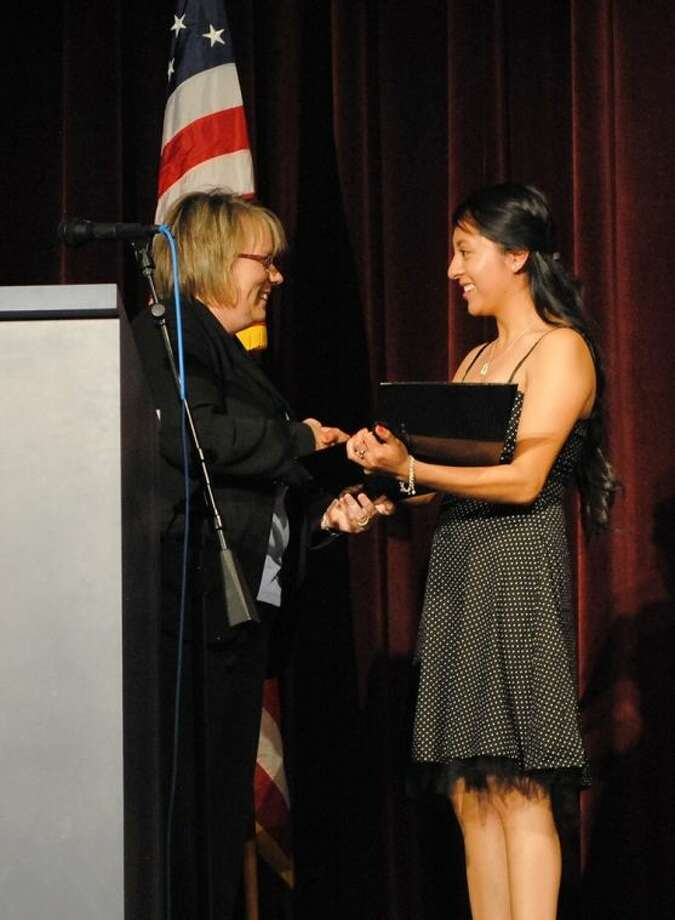 ACC Foundation Executive Director Wendy Del Bello, left, hands a scholarship award to Alvin High School student Miriam Higuera during Award Night at the school in 2013.