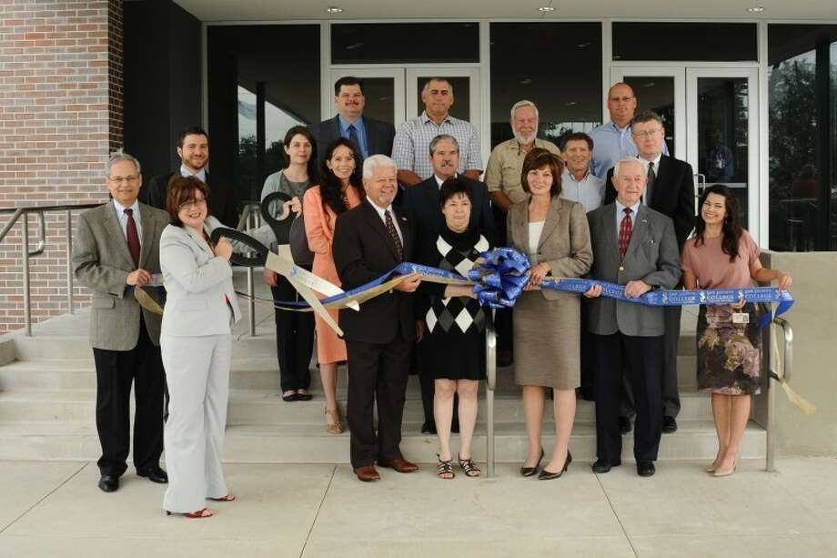 Local elected officials, school officials and contractors stand as San Jacinto College South Campus President Dr. Maureen Murphy ceremoniously cuts the ribbon dedicating a new Welcome Center and Academic Hall during a ceremony Tuesday, May, 15.