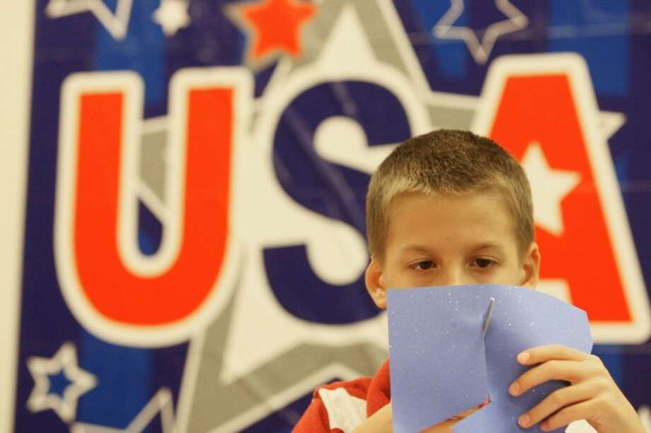 Landry Hixson, 9, of The Woodlands, cuts out a paper star during Vacation Liberty School Monday at the Tea Party Patriots PAC in The Woodlands.