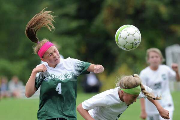 Sacred Heart's Anna Snopkowsi, left, advances the ball with a header over Greenwich Academy defender Katherine Goldsmith on Wednesday.