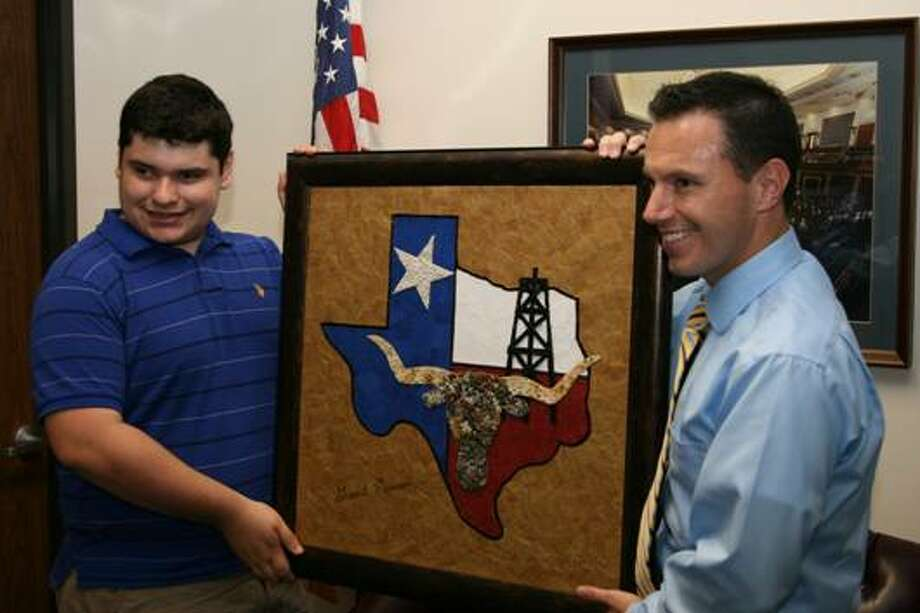 "Grant Manier presents ""Texas, Our Texas"" to Congressman Brady's Deputy District Director Russell Martinez."