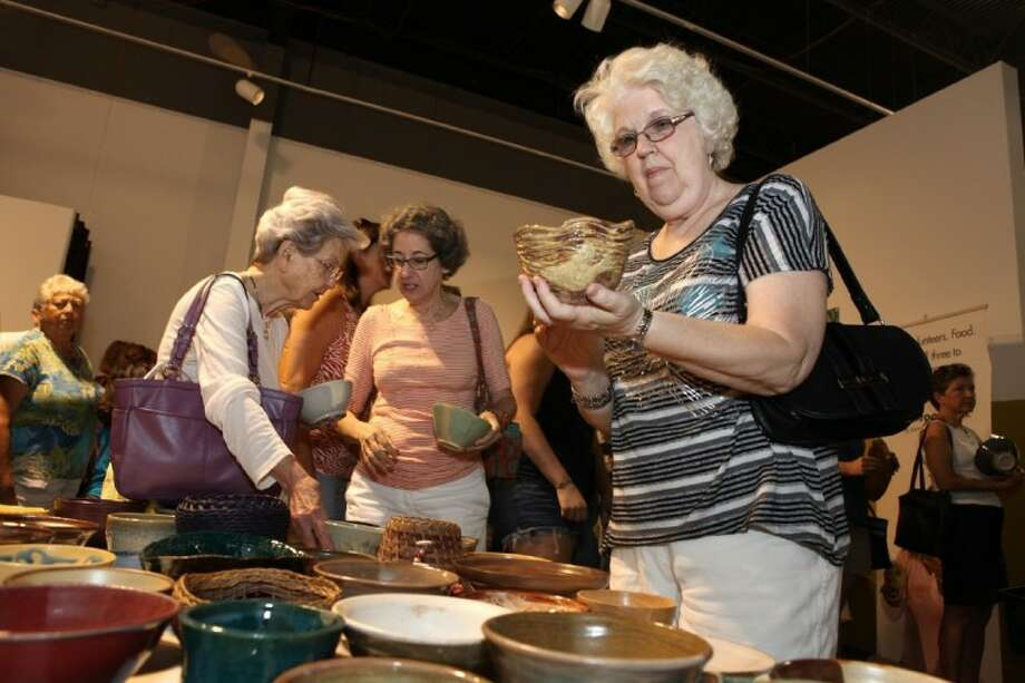 Mary Ramer of Spring looks at a bowl as she shops at the 8th Annual Empty Bowls Houston at Houston Center for Contemporary Craft Saturday.