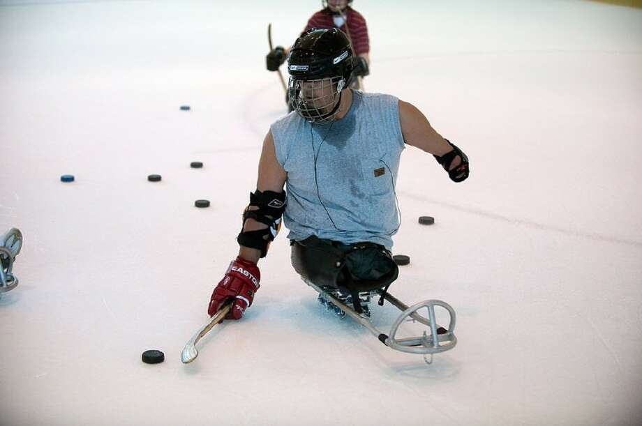PHOTO BY FRED TRASK:Joseph Montemayor practices Sled Hockey at the Memorial City Mall.