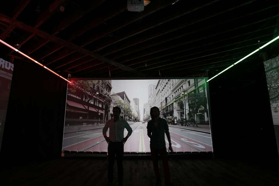 Artists Stefano Corazza, (left) and Gearge Zisiadis against their conception of  what the installation will look like when completed, using video projection of Market St. and streaking colored lights moving along the roadway, seen in San Francisco, California on Wed. Sept. 28, 2016. The people who brought us the Bay Lights on the Bay Bridge intend to run lights up and down Market St. Photo: Michael Macor, The Chronicle
