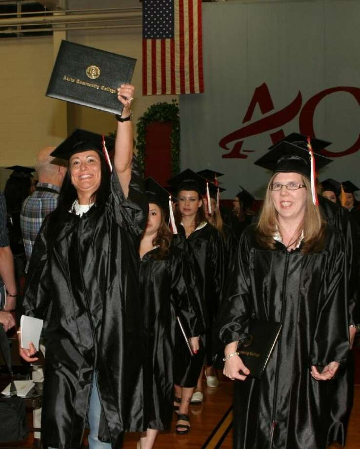 An ACC graduate, left raises her college diploma after the Commencement ceremony in 2012.