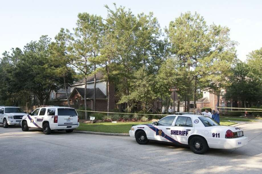 Police investigate the scene of a probable murder-suicide at a home on West Greenvine Court in The Woodlands Monday.
