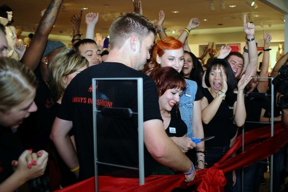 H&M employees cheer as Ladies Department Manger Lindsay Bealle cuts the ribbon to officially open the new store at Baybrook Mall Friday, May, 31.