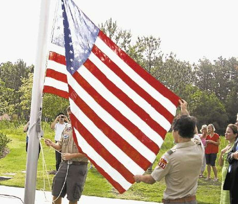 Boy Scouts raise the United States and Texas flags on the pole outside of the Kingwood Library. Both were donated to the library by Congressman Ted Poe and State Representative Dan Huberty after they were flown over each respective capitol in honor of the library.