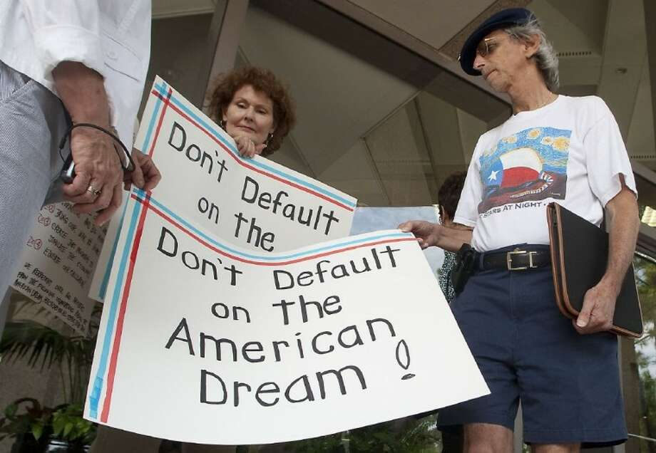 Kay Bonham and David Wald hold signs outside Culberson's local office in the Memorial area Tuesday afternoon, urging him to support a deal on the debt crisis. Photo: PATRIC SCHNEIDER