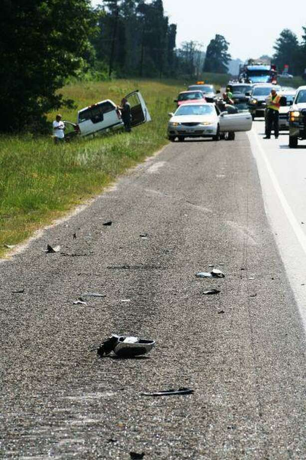 Debris is scattered along Texas 105 following a two-car crash on Wednesday. One driver was transported to a local hospital; the other driver reportedly was not seriously injured.