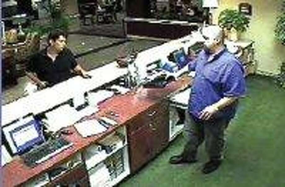 A surveillance camera at the Holiday Inn Express in the 24800 block of Interstate 45 North captured this image of an armed man, left, as he approached the clerk and demanded money.