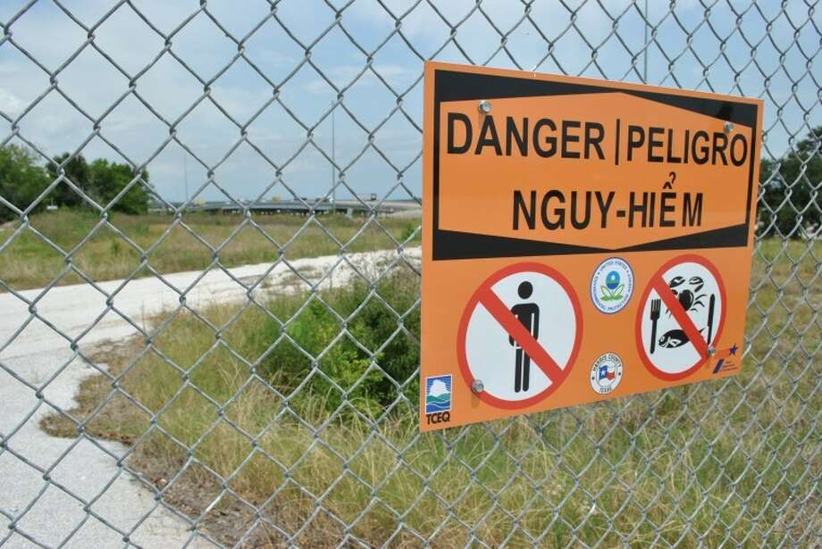 A sign on a fence erected around the San Jacinto River Waste Pits (in the background is the I-10 bridge) advises against eating fish or crabs from the river.  -Photo by Florian Martin/The Citizen