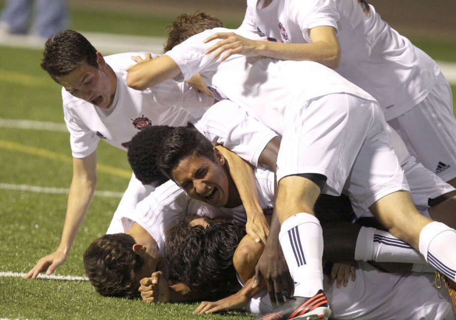 Seven Lakes players swarm Thomas Barboza after scoring on a header to defeat Jersey Village in their Region III-5A area playoff April 5 at Rhodes Stadium in Katy. The Spartans won 3-2. Visit www.hcnpics.com for more photos. Photo: Alan Warren/HCN