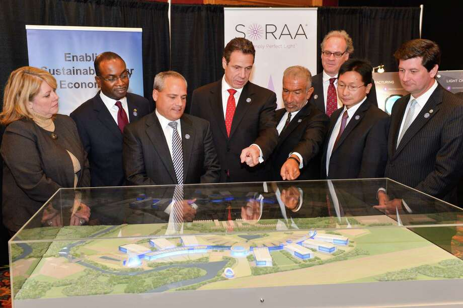 Gov. Cuomo, center, stands with Alain E. Kaloyeros, right, as he announces that part of his Buffalo Billion initiative New York State will build a state-of -the -anchor hub facility for high tech and green energy businesses at Riverbend in the city of Buffalo on Nov. 21, 2013, in Buffalo, N.Y. (Office of the Governor) / © Office of the Governor