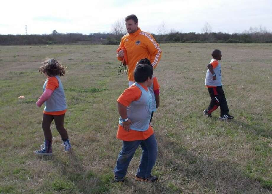 Students shown on the soccer field with Dynamo Nathan Thackeray.