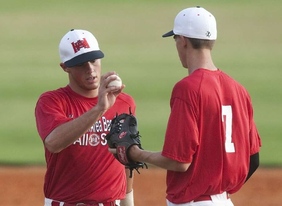 PHOTO BY PATRIC SCHNEIDER/The Sun: Memorial High third baseman/pitcher Ben Carl, left, helped lead the Red team to a 4-0 victory over the Blue squad in the HABCA Junior Futures All-Star Game on Wednesday night at Baseball USA.