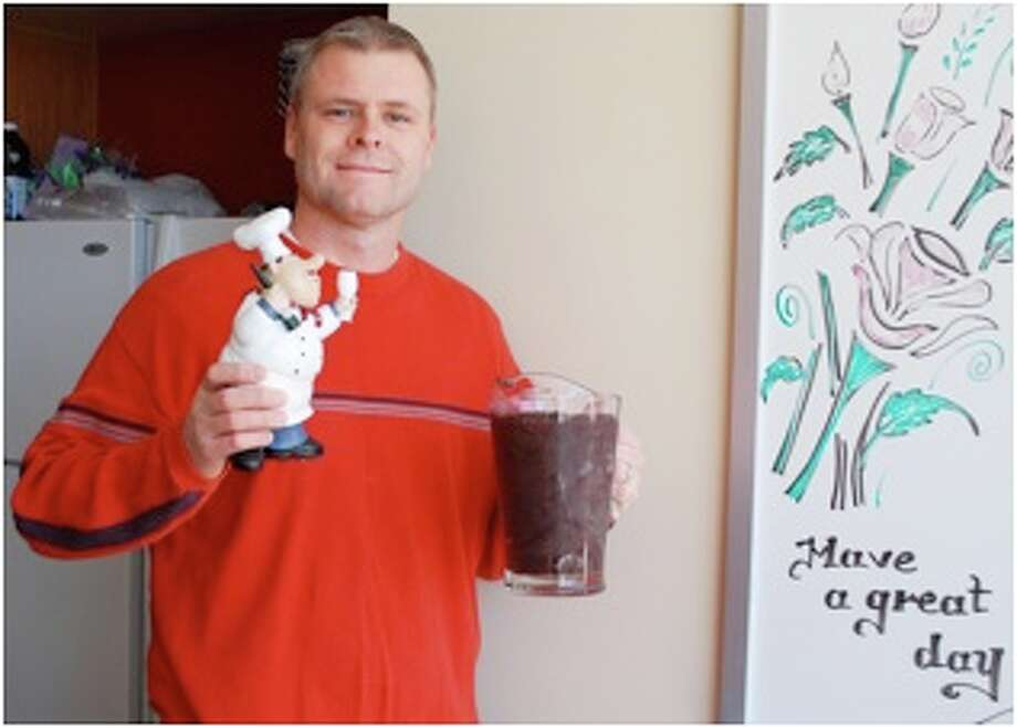 """MD Anderson Regional Care Center Nurse Tom Bleyendaal poses with a trophy he won after he and other staff members competed in a healthiest smoothie competition. The competition was held after months of popular """"healthy smoothie Fridays"""" the staff was using as a way to promote office wellness and health. Photo: Submitted Photo"""