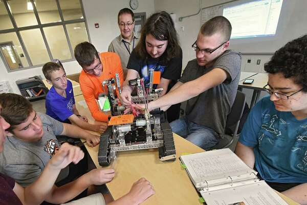 Teacher George Reluzzo, fourth from right, watches his students work on a robot in his engineering design and development class at the Center for Advanced Technology at Mohonasen High School on Tuesday, Sept. 27, 2016 in Schenectady, N.Y. The $48.2 million capital project comes equipped with lab spaces for students interested in careers in technology (electrical, machining, manufacturing, nanotechnology), media, science and health professions. Depending on the field, students will have the option to earn college credit or to work toward a professional certificate. Evening courses will also be available for adults in the region.(Lori Van Buren / Times Union)