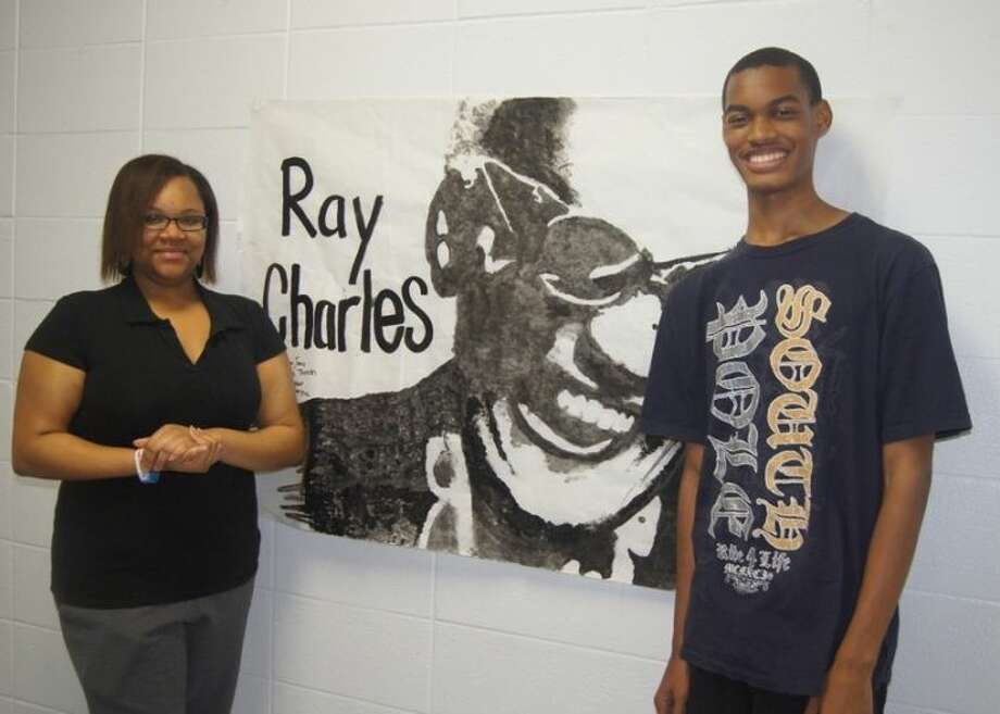 WHS sophomores Chelsea Thrash and Andrew Jones stand beside a painting they created with their classmates Jordan Hadnot and Isaac Rodriguez.