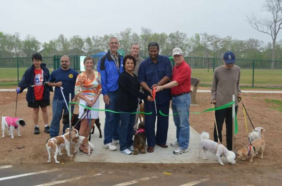 Pictured Left to Right: Betty with dog Patches, Aaron Rodriguez, Fort Bend Animal Services; Susan Fox; Commissioiner Precinct 4 James Patterson, Dr. Mary Desvignes-Kendrick, Fort Bend County Health and Human Services Director; Commissioner Precinct 2 Grady Prestage; Commissioner Precinct 3 Andy Meyers; Eric with dogs Po, Suki and Jasper.
