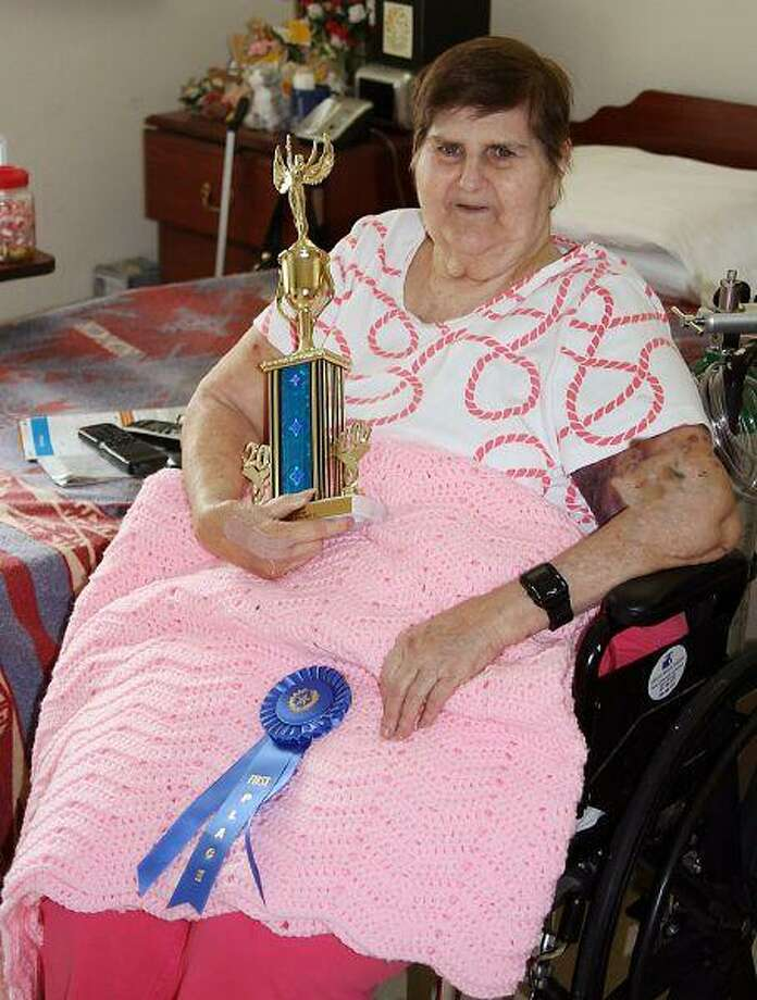 Park Manor resident Carol Patterson shows off the trophy and ribbon she earned as the first place winner for the crocheted afghan she presented at the Senior County Fair. Patterson is legally blind but beat other competitors this year to be the first Park Manor resident to win at the fair.