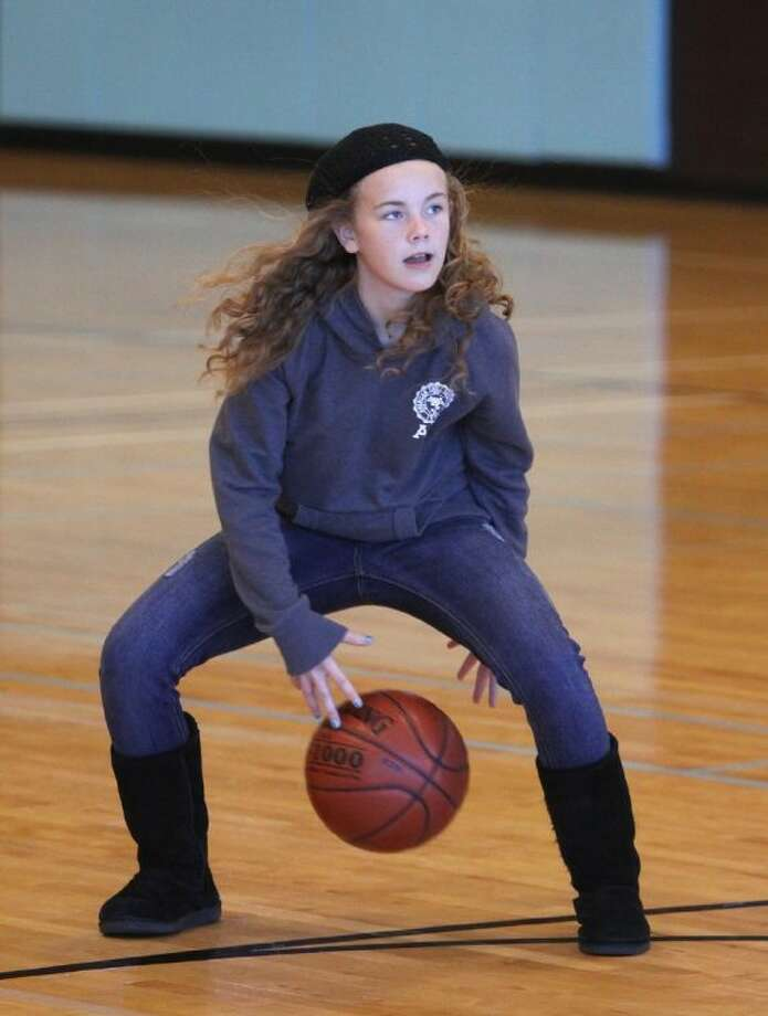 Avery Smith 10, of Richmond dribbles around as her brother, Hudson attends a National Basketball Academy and Houston Rockets Clinic at Imperial Park Recreation Center in Sugar Land. (Photo by Alan Warren) Photo: Photo By Alan Warren