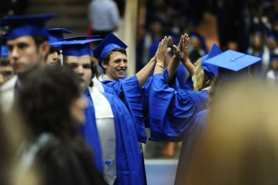 Storm Gordon offers a 'high five' to a fellow graduate during the Friendswood High School graduation ceremony Saturday, Jun. 2.