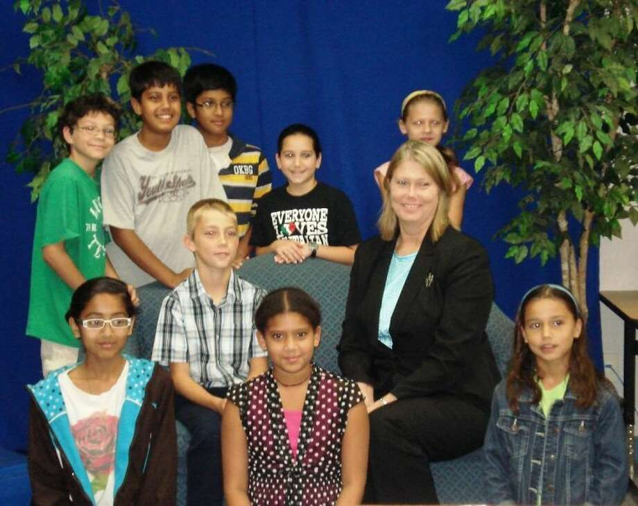 "Dr. Rhonda McWilliams, FBISD Assistant Superintendent (shown second row, from right), served as the first guest for the new ""Focusing on Fort Bend"" segment produced by the BBE Kids News Team. She is pictured with (front row, from left): Safa Ali, Nisha Walimomin, Sumer Brito; (second row, beside McWilliams) Lucas Equitz; and (back row) Grant Ligon, Zul Sakhiyani, Nibu Varghese, Alyssa Consoli, Grace Newman. Photo: Submitted Photo"