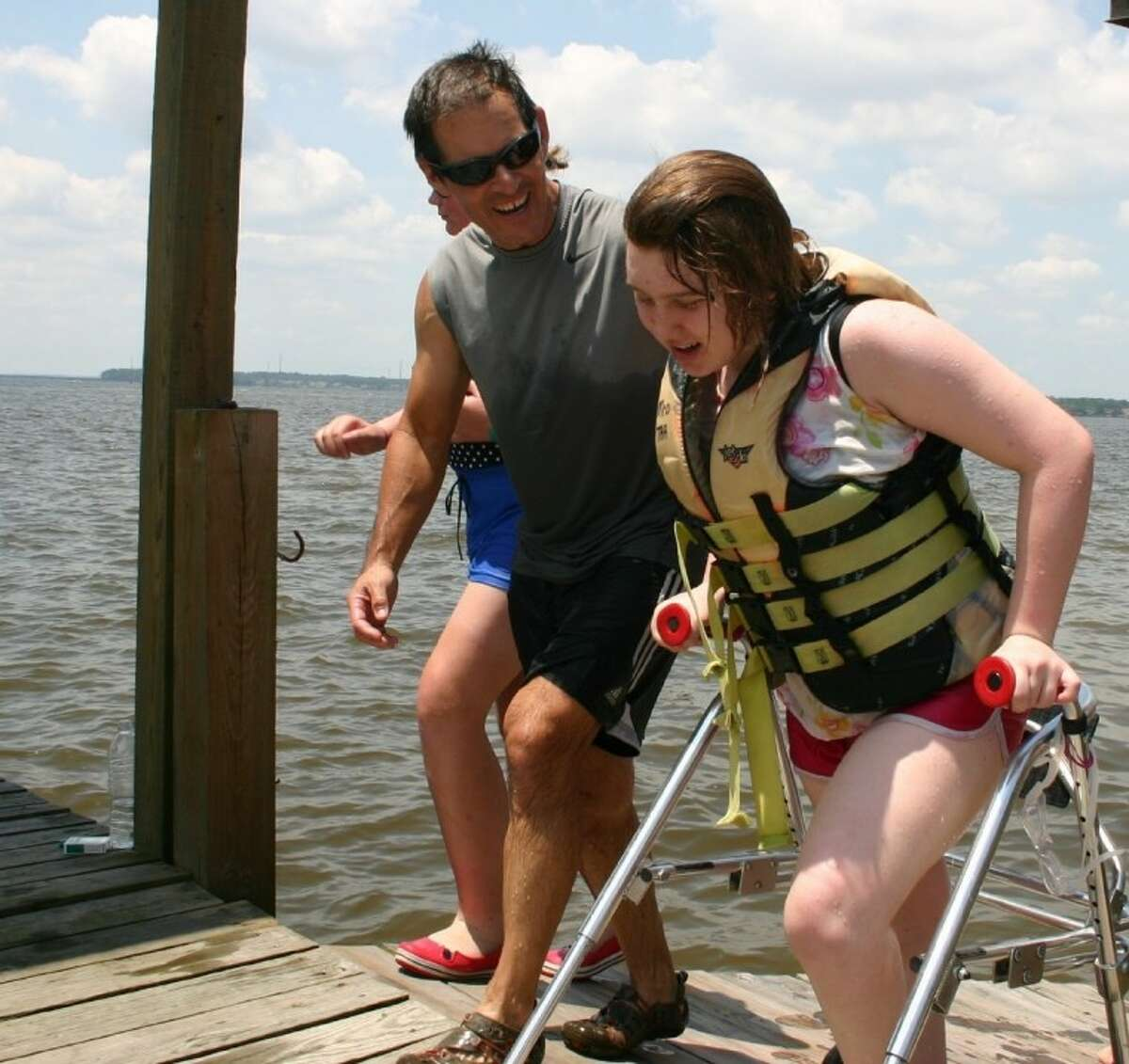 Patrick Fries asks his 14-year-old daughter, Claire, how her water skiing on Lake Houston went June 2 at Texas Adaptive Aquatics in Huffman. Claire has cerebral palsy.