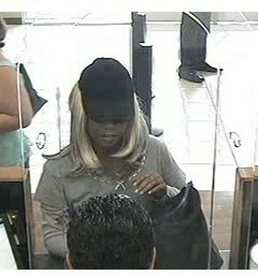 This robber captured on surveillance cameras was dressed like a woman, but eyewitnesses told authorities the suspect was a man.