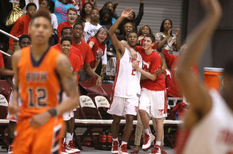 The Travis bench begins to celebrate during the closing seconds of its Region III-5A championship victory against Bush, March 2 at the M. O. Campbell Center in Houston. The Tigers defeated South Grand Prairie 46-38 on March 9 to win the Class 5A state championship.