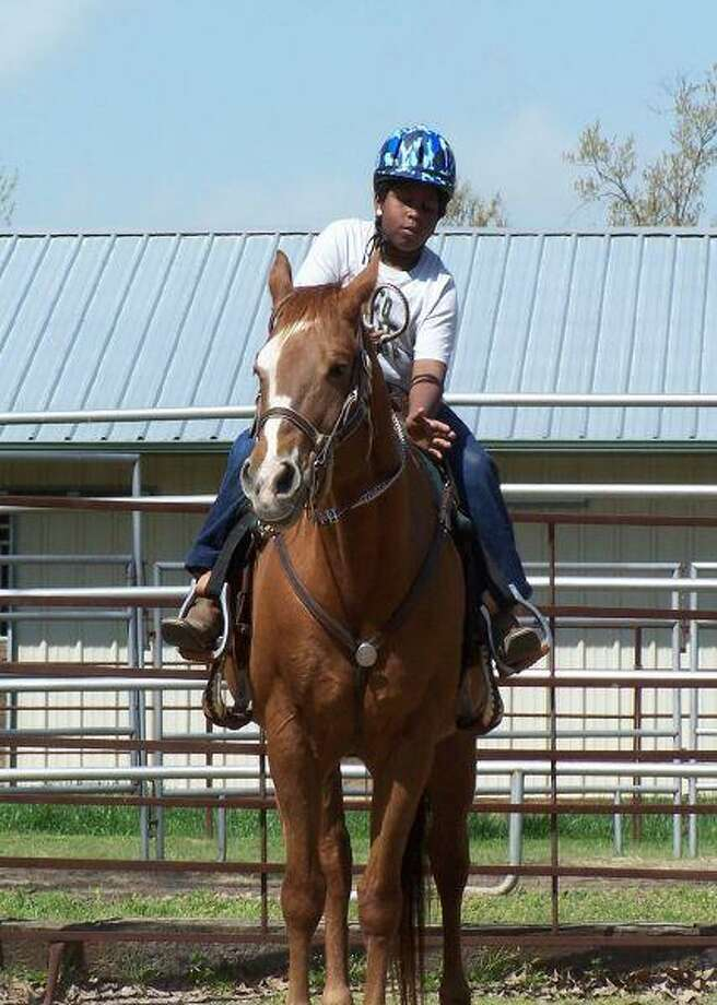Eugene Reyes, 11, of Montgomery gives horse 'Reba' a pat after completing a riding task. Reyes had fun honing his horsemanship skills at a recent boys' camp at All The King's Horses, an equestrian outreach program in Montgomery County.