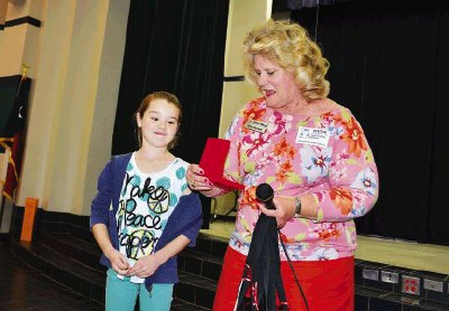 Zaner-Bloser regional sales representative Diane Dunbar presents Sampson Elementary School third-grade student Emma Farmer with an engraved state winner medallion for being the state winner in the Zaner-Bloser Handwriting Contest.