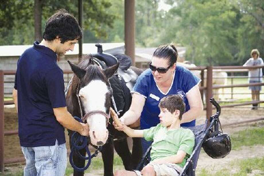 SIRE Volunteer Chris Jardine, SIRE Site Director Shayna Bolton and rider Garrett interact with Rudy after a morning ride.