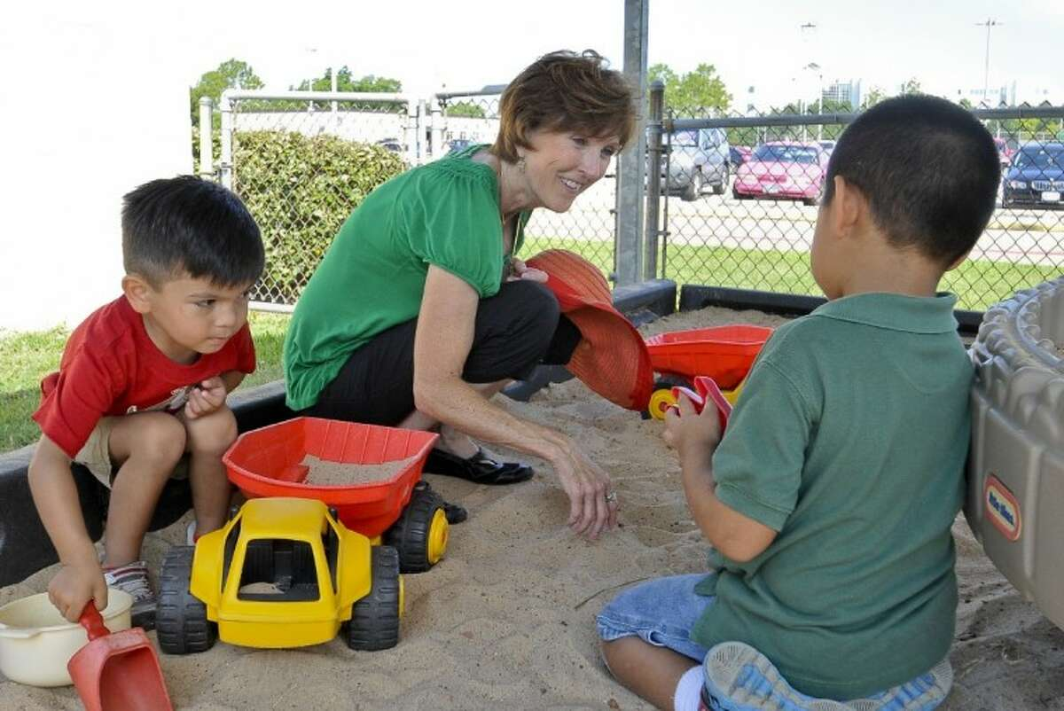 San Jacinto College South Campus children's center teacher, Nancy Hutchinson, joins students Noah Enriquez (left) and Gabriel Lopez (right), playing in the sandbox. Hutchinson is a finalist for the inaugural Bammy Awards, presented by the Academy of Education Arts and Sciences. Photo credit: Andrea Vasquez, San Jacinto College marketing department.