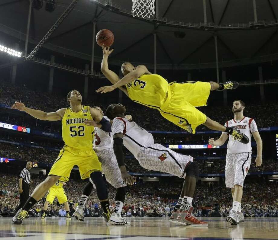 Michigan guard Trey Burke (3) shoots over Louisville center Gorgui Dieng (10) during the second half of the NCAA Final Four title game. Louisville won 82-76.