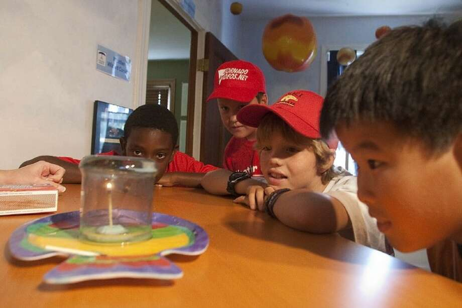 (From left - right) Christopher Hughes, 8, Brennan Fane, 10, Paul Houston, 8, and Andrew Chan, 10 watch closely as camp director Monica Krausz (not pictured) conducts a low pressure experiment during a Hurricane Central camp at the Weather Research Center on Caroline Street on Friday morning. The camp is designed to let area children learn the science behind tropical storms and hurricanes. In this experiment, the lighted match creates a low pressure, sucking up water that was placed on the plate into the covered glass. The same way a tropical storm or hurricane does.